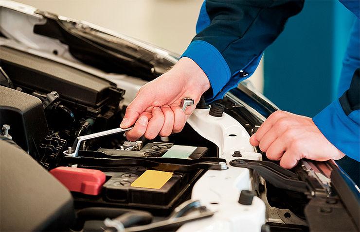 hombre desconectando bateria coche
