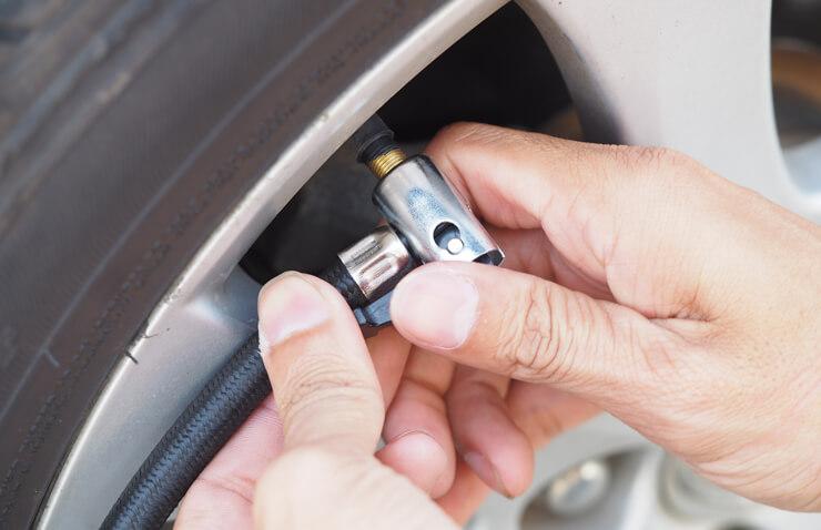 persona inflando neumáticos coche
