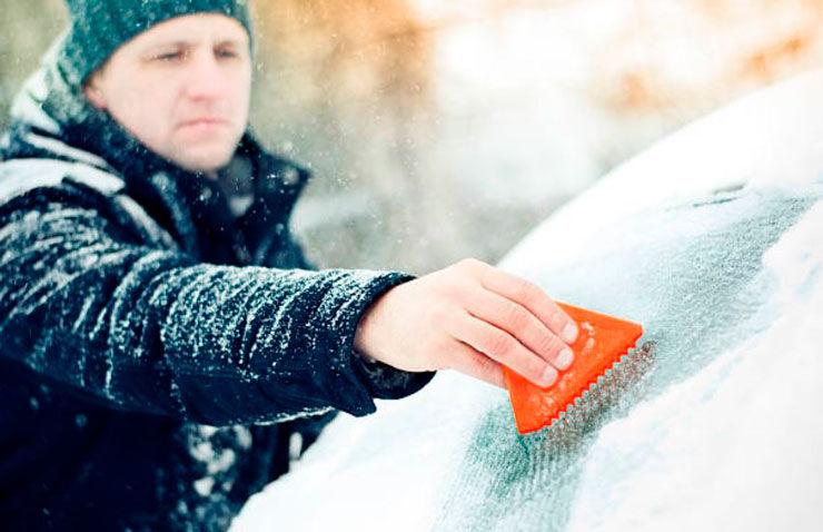 hombre quita hielo parabrisas
